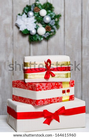 Stack of wrapped gift boxes with ribbons and Christmas wreath hanging on the wall behind - stock photo