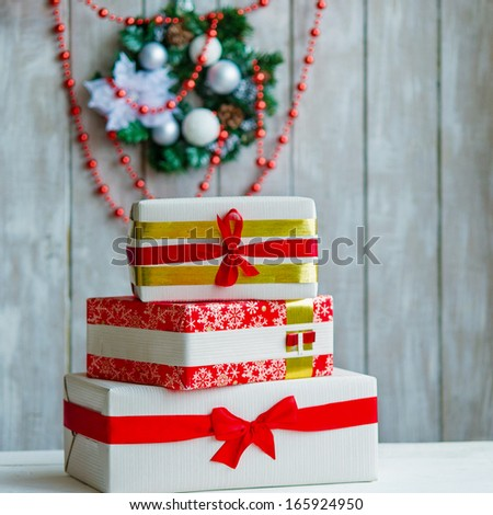 Stack of wrapped gift boxes with ribbons and Christmas wreath with red beads hanging on the wall behind - stock photo