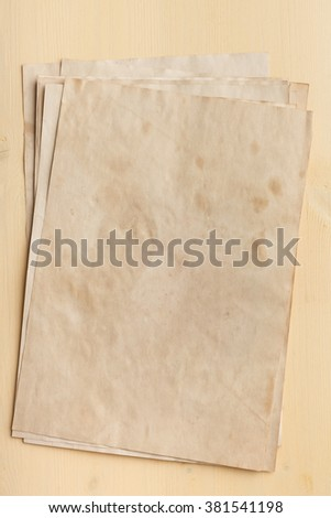 Stack of yellowed old paper on a wooden table