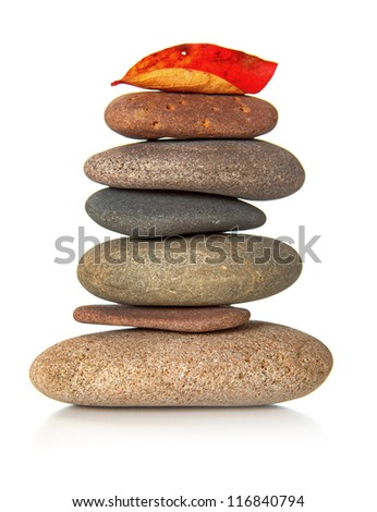 Stack of zen stones with red dry leaf on top - stock photo