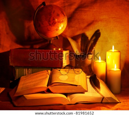 Stack old book and candle. Education. - stock photo