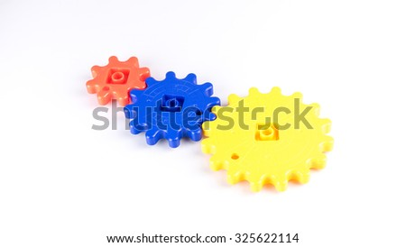 Stack or arrangement of cute and colourful plastic gears or cogwheel. Isolated on white background. Concept of process and rotating mechanism. Slightly de-focused and close-up shot. Copy space. - stock photo