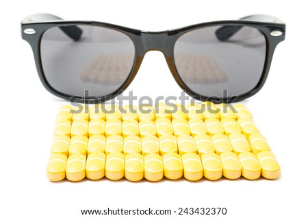 Stack or pills and sunglasses isolated on white background - stock photo