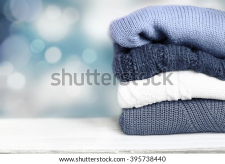 Stack pile of knitted winter clothes on wooden blur background empty space for text.Cozy autumn fall textile. - stock photo
