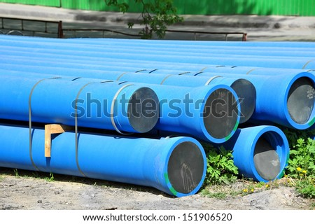 Stacked blue PVC pipe on construction site - stock photo