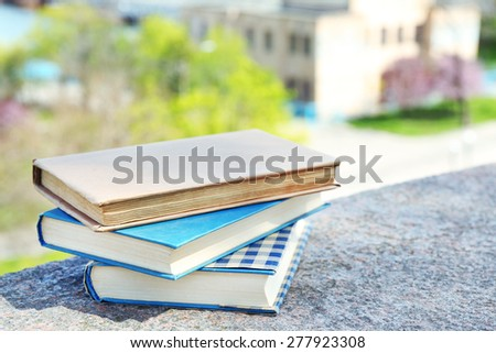 Stacked books on bright background - stock photo