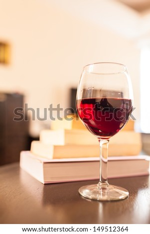 Stacked books with glass of wine