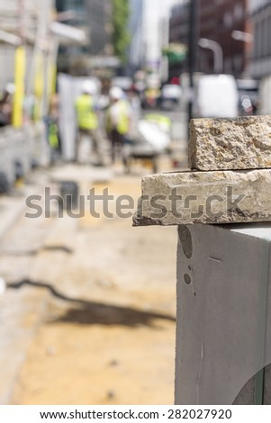 Stacked bricks in foreground with construction worker out of focus in background - stock photo