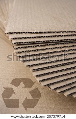 Stacked cardboard with recycle symbol - stock photo