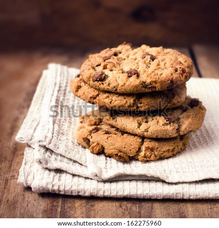 Stacked chocolate chip cookies on white napkin in country style. Chocolate chip cookies shot on wooden table with selective focus. - stock photo