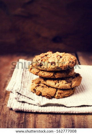 Stacked chocolate chip cookies on white napkin over wooden background in country style.  - stock photo