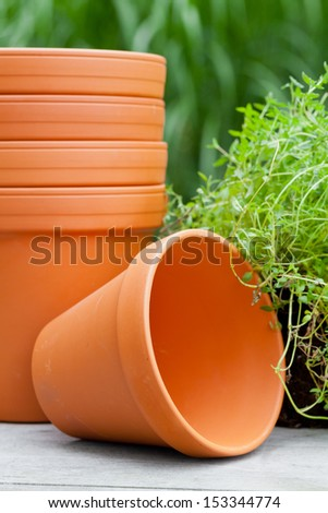 Stacked empty plant pots and herbs on garden table - stock photo