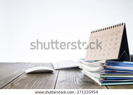Stacked files with calendar.Office supplies on wooden office desk. - stock photo