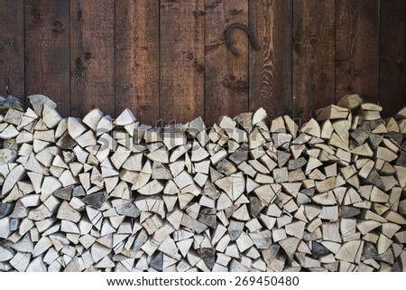 Stacked fire wood and barn wall with horse shoe/Oak wood stacked for fire/Oak tree wood stacked for fire in the barn with horse shoe - stock photo