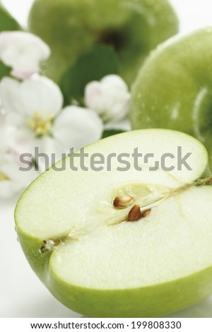 Stacked green apples, and apple blossom - stock photo