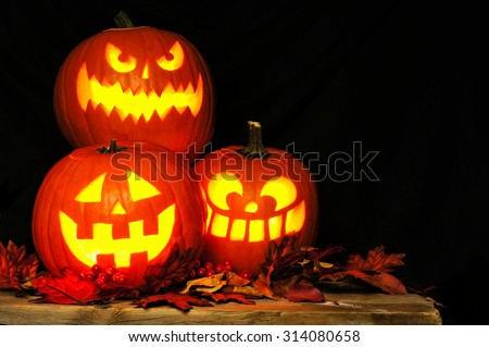 Stacked Halloween Jack o Lanterns illuminated at night with old wood and autumn leaves - stock photo