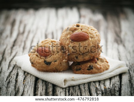 Stacked homemade almond cookies on wooden table background.