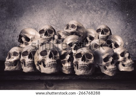 Stacked human skulls on old wooden table in front of grunge concrete wall - stock photo