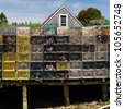 Stacked Lobster traps and buoys on a Maine dock at low tide - stock photo