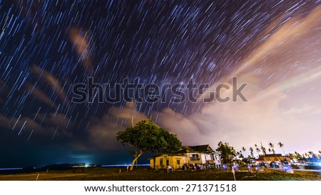 Stacked of images of milky way and stars produced colorful star trails in Kuala Terengganu, Malaysia. Isolated house in the foreground - stock photo