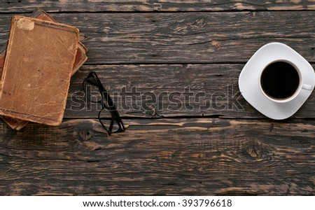 stacked old books, eyewear and cup of coffee on a dark wooden table, top view with copy space - stock photo