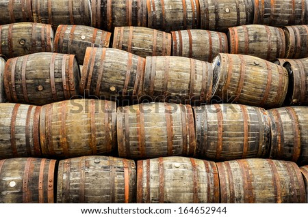 Stacked pile of old whisky and wine wooden barrels and casks - stock photo