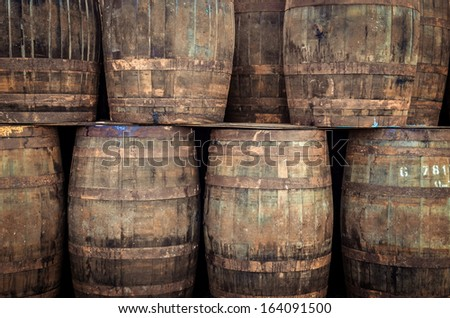 Stacked pile of old whisky barrels - stock photo