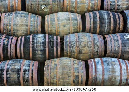 Stacked pile of old wooden barrels and casks at whisky distillery in Scotland.