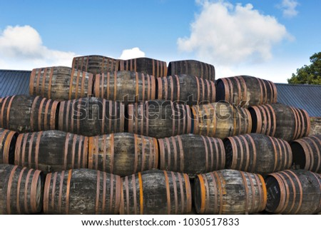 Stacked pile of old wooden barrels and casks under open sky at whisky distillery in Scotland.