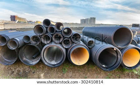 stacked pipes in construction site - stock photo
