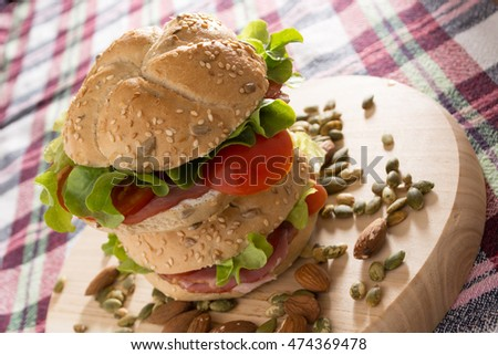 Stacked sandwiches with fresh smoked meat, cheese, lettuce and tomato with homemade ketchup arranged with almond and pumpkin seeds