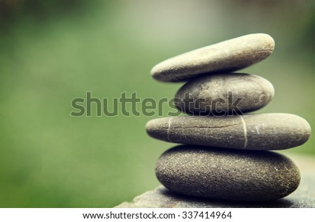Stacked spa stones with a nature green background. - stock photo
