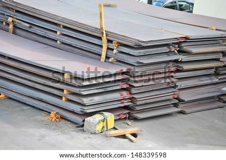 Stacked steel metal sheet, ready for shipment in port - stock photo