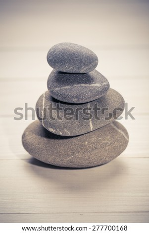Stacked stones on a  natural wooden background - stock photo