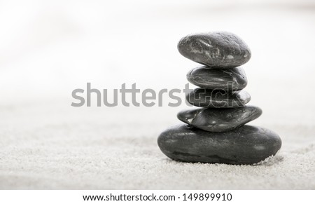 Stacked stones on sand in a Japanese ornamental or zen garden.