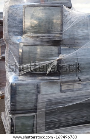 Stacked televisions wrapped on a palette for electronic recycling - stock photo