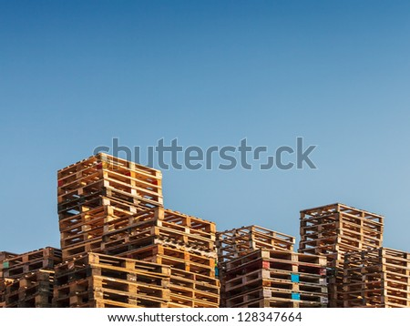 Stacked up colorful wooden cargo pallets against a blue sky - stock photo