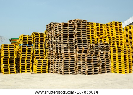 Stacked up wooden pallets at cargo with blue sky. - stock photo