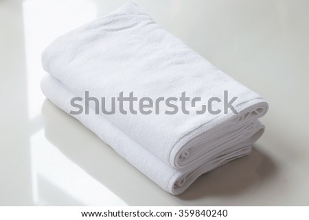 Stacked white spa cloth beach towels on marble  background.