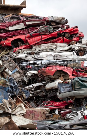 Stacked wrecked cars going to be shredded in a recycling facility