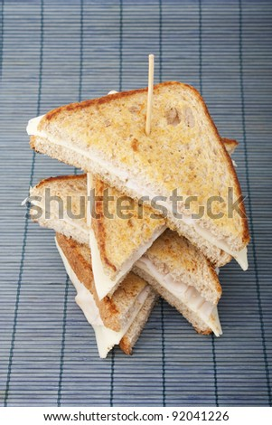 Stacking sandwiches of smoked turkey ham with cheese - stock photo