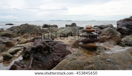 stacking stones on the beach with rock background