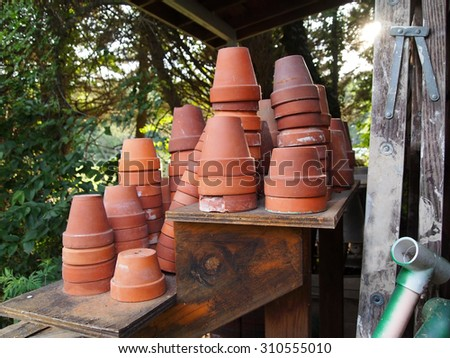 Stacks and stacks of small empty clay flower pots next to a gardening shed in the late day sun. - stock photo