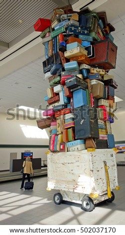 "Stacks of abandoned suitcases in an airport baggage claim area, make for an interesting modern ""pop"" art sculpture."