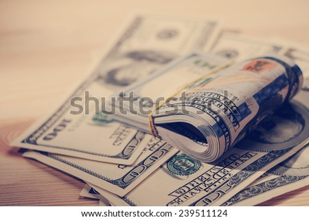 Stacks of american money / studio photography of US banknotes - on wooden background. 100 dollar bills close up. Instagram style. - stock photo