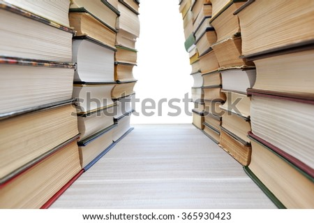 Stacks of books making a corridor with white copyspace in the end