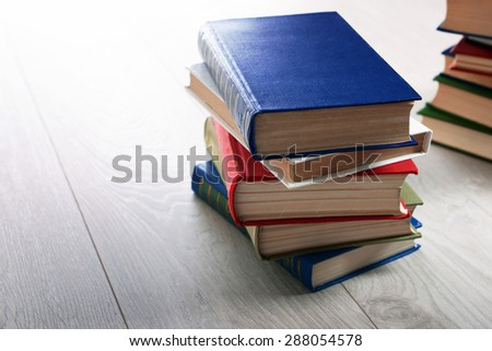 Stacks of books on wooden background - stock photo