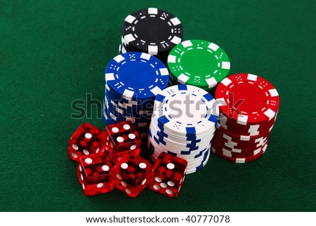 Stacks of casino chips and dice on green