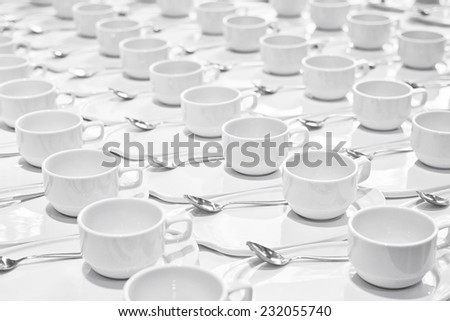 Stacks of coffee cups  with silver teaspoons  prepare for meeting - stock photo