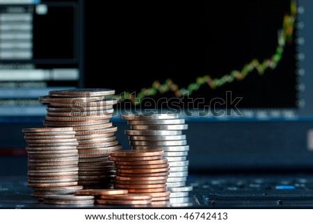 Stacks of coins  and a up trend chart as the background - stock photo